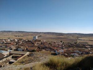 Típico pueblo monegrino. Campos de cultivo y montes sin árboles.